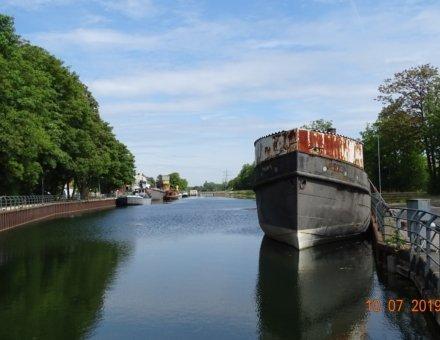 Hier erkennt man ein großes altes älteres Boot auf einem Fluss. Auf der rechten Seite säumen groß Buchen den Fluss.