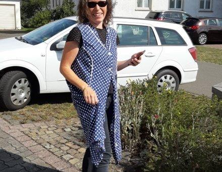 Auf dieser Aufnahme ist eine Teilnehmerin, als Schmugglerin abgebildet. Sie trägt eine blaue Schürze mit weißen Punkten. Sie lacht in die Kamera.