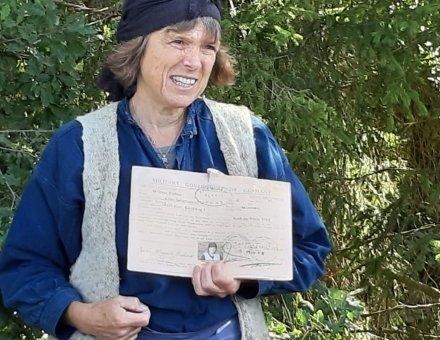Auf diesem Bild hält Anna Grenze ein Dokument in den Händen. Sie ist blau angezogen und trägt die Kleidung wie früher. Auf dem Kopf trägt sei ein blaues Kopftuch.