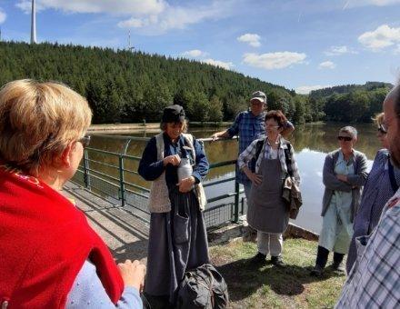 Hier zeigt Anna Grenze was früher alles geschmuggelt wurde. Im Hintergrund ist ein Windrad, eine kleine Brücke und ein See.