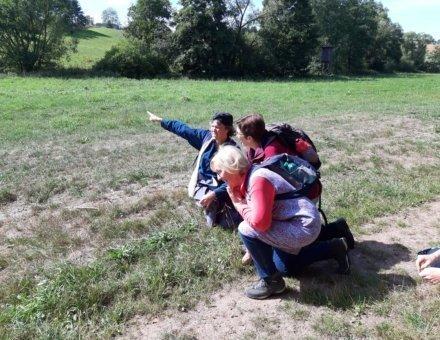 Dieses Bild zeigt wie man sich früher verhalten musste, um nicht entdeckt zu werden. Anna Grenze und unsere Ehrenamtlichen Odette und Resie sitzen gebückt auf einer Wiese.