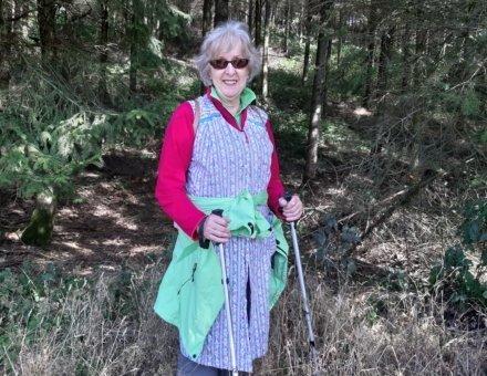 Dieses Bild zeigt unsere Ehrenamtliche Constance. Sie trägt eine schöne Omaschürze und hat Wanderstöcke in den Händen. So sahen früher die Frauen aus, wenn sie schmuggelten.