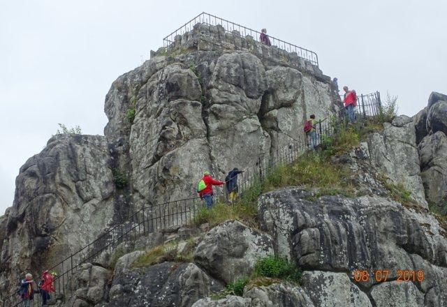 Dieses Bild zeigt wie einige Teilnehmer einen großen Felsen besteigen.