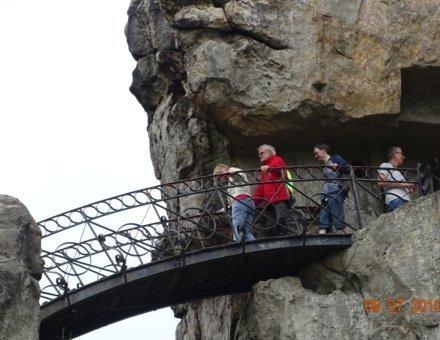 Hier gehen Teilnehmer und ein Ehrenamtlicher über eine kleine Brücke, die zwei Felsen verbindet. Es sieht spannend aus.