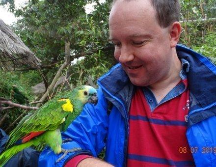 Dieses Bild zeigt Teilnehmer Christoph. Er hat einen grünen Papagei auf seinem rechten Arm. Er lächelt.