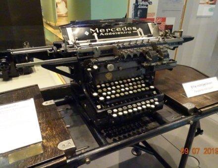 Hier ist eine uralte Schreibmaschine abgebildet. Sie ist groß und schwarz und steht auf einem alten Schreibtisch.