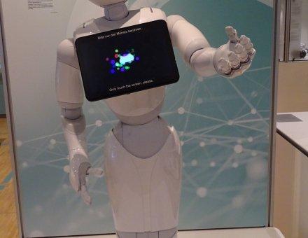 Hier ist ein Roboter abgebildet. Er ist ganz weiß. Auf seiner Brust hängt ein Ipad (man sagt Ei pätt)