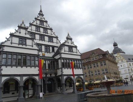 Hier ist ein historisches Gebäude abgebildet. Das Gebäude befindet sich an einem Platz mit einem Brunnen. Im Hintergrund erkennt man weitere historische Gebäude.