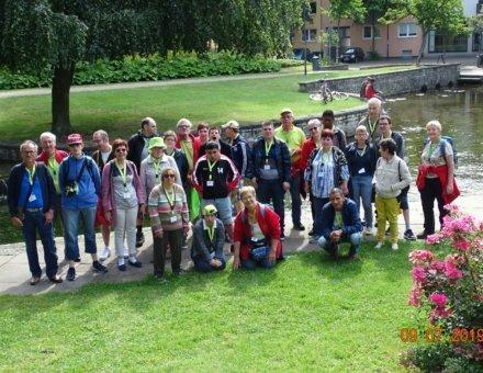 Auf diesem Foto ist die ganze Reisegruppe abgebildet. Sie stehen in einer schönen Parkanlage. An der rechten Seite ist ein See und ein Strauch mit rosa Blumen.
