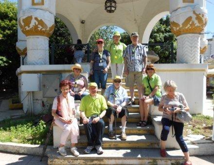 Auf diesem Foto sitzt ein Teil der Feriengruppe auf der Treppe eines Sonnenpavillons. Die Sonne scheint und die Farben der Kleidung leuchtet.