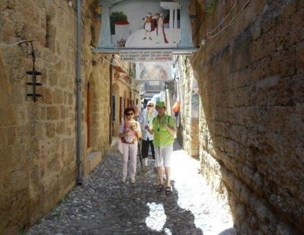 Die Teilnehmer spazieren durch einer Gasse. Man kann einen Sonnenstrahl erkennen.