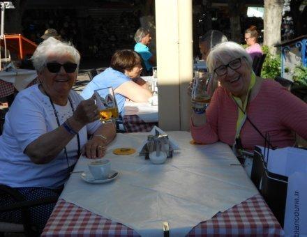 Prost! Zwei Teilnehmer trinken sich gemütlich ein Bier auf einer sonnigen Terasse.
