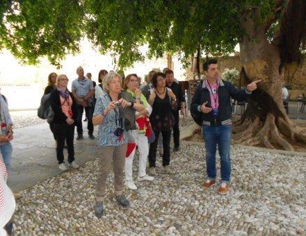 Das Foto zeigt unsere Reisegruppe bei einer Führung. Die Teilnehmer hören interessiert zu und machen Fotos.