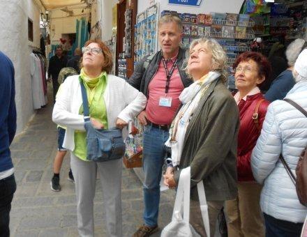 Die Teilnehmer befinden sich vor einem Geschäft. Alle schauen nach oben. Was sie sich anschauen bleibt leider ein Rätsel.