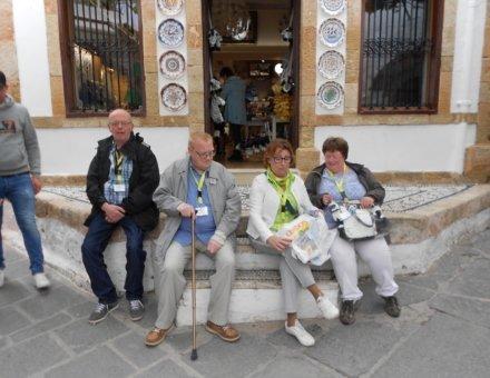 Auf diesem Bild sitzen vier Teilnehmer auf einer Treppe vor. Der Eingang des Geschäftes ist mit bunten Teller dekoriert.