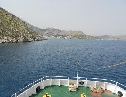 Dieses Bild wurde auf einem Schiff gemacht. Man erkennt den Bug des Schiffes und das blaue Meer. an der linken Seite sieht man grün bewachsene Felsen.
