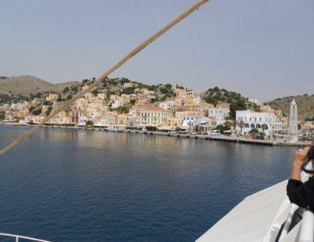 Tolles Foto vom Schiff aus mit Aussicht auf einem kleinem Ort. Die Häuser sind direkt am Wasser. Hinter den Häusern sind grün bewachsene kleine Berge.