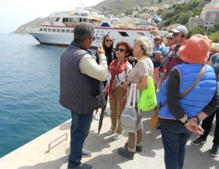 Auf diesem Bild stehen die Teilnehmer am Kai. Im Hintergrund liegt ein großes Schiff auf den tiefblauen Meer.