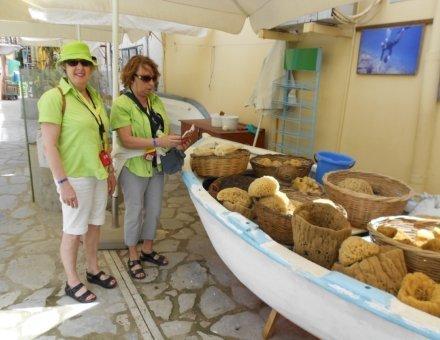 Hier befinden sich zwei Ehrenamtliche Denise und Constance vor ein Boot mit Naturschwämmen. Beide haben grüne Blusen an, die leuchten. Eine der Beiden (Constance) hat einen grünen Sonnenhut an.