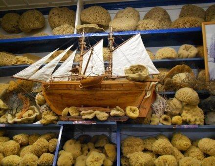 Auf diesem Foto ist ein kleines Segelschiff abgebildet. Es liegt auf einer Kiste mit Naturschwämmen. Die Schwämme sind nach Größe und Qualität in blauen Fächern sortiert.