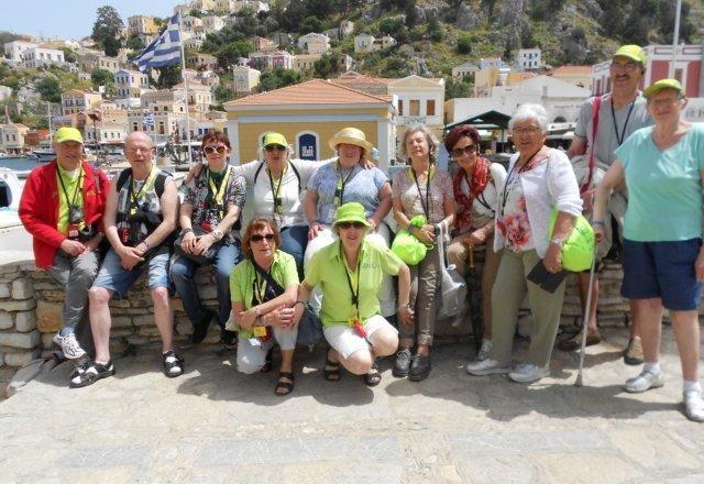 Auf dieses Foto befinden sich die Teilnehmer vor einer tollen Aussicht. Man erkennt im Hintergrund die typischen kleinen gelben Häuser und die griechische Landesfahne.