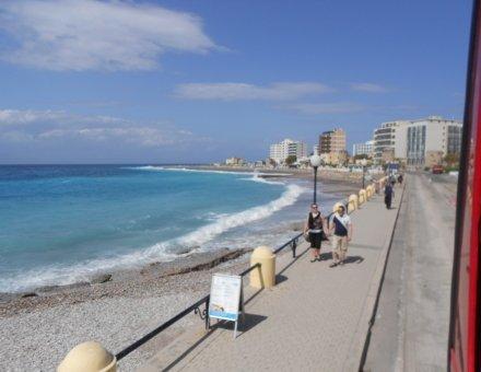 Dieses Foto zeigt ein hellblaues Meer und Spaziergänger auf der Strandpromenade. Der Himmel ist ebenfalls strahlend blau und mit weißen Schleierwolken bedeckt.