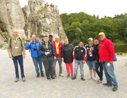 Dieses Foto ein Gruppenfoto. Die Teilnehmer stehen vor einem Felsen.