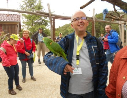 Hier erkennt den Teilnehmer Jochen. Er lächelt. Auf seinem rechten Arm sitzt ein grüner Papagei. Im Hintergrund stehen andere Teilnehmer sowie ein blauer Papagei.