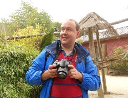 Hier steht der Teilnehmer Christoph. Er hat einen grünen Papagei auf seiner rechten Schulter und einen Fotoapparat in seinen Händen. Er schaut den Papagei etwas skeptisch von der Seite an.