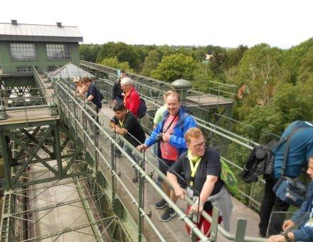 Auf diesem Foto stehen einige Teilnehmer auf einer Aussichtsbrücke eines Werkes.