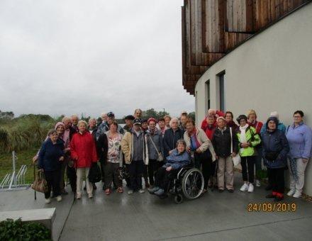 Dies ist ein Foto von der ganzen Gruppe. Die Teilnehmer stehen vor dem Hotel. Alle haben ein Lächeln im Gesicht.