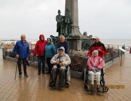 Auf diesem Bild stehen die Teilnehmer vor einem großen Denkmal. Trotz Regen haben sie ein Lächeln in ihren Gesichtern.
