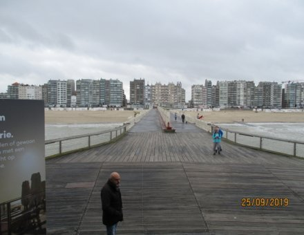 Der Fotograf befindet sich auf dem bekannten Holzsteg in Blankenberge. Er fotografiert Richtung Strand. Man sieht die Wohnblocks am Strand. Links und rechts vom Steg ist das Meer.