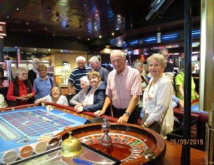 """Auf diesem Foto sind die Teilnehmer im Casino. Sie spielen """"Roulette""""."""