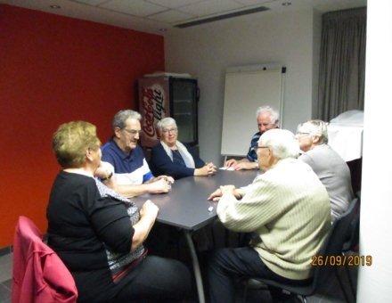 Die Teilnehmer sitzen an einem Tisch und spielen gemeinsam ein Kartenspiel.