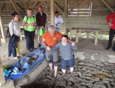 Auf diesem Foto sieht man Teilnehmerin Myriam mit dem Ferienbegleiter Paul. Beide gehen mit nackten Füssen durch Schlamm. Beide lachen. Andere Teilnehmer schauen zu.