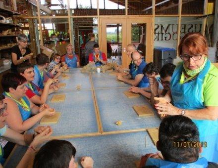 Auf diesem Foto sitzen die Teilnehmer um einen großen Tisch. Sie kneten Männchen aus Ton. Rechts ist Ferienbegleiterin Denise. Sie erklärt wie man Tonmännchen herstellt.