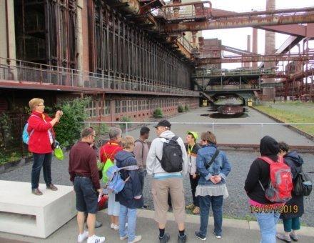 Auf dem Foto sind die Teilnehmer auf dem Gelände der Zeche Zollverein Essen. Sie werden von der Ferienbegleiterin Christel fotografiert.